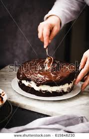 triple chocolate layer cake hand dipping stock photo 615846230