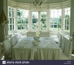 cream slip covers on chairs in country dining room with linen