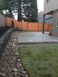 concrete patio river rock border with drainage and lawn for the