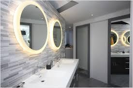 round bathroom mirror with light above wood vanity using storage