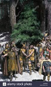 european tribesmen bringing in the first christmas tree stock