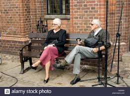 older couple sitting on bench in torun poland while waiting for