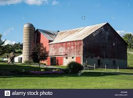 amish farm with red barn and silo along rural road in holmes