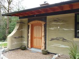 cedar log entry and fir and maple door on a beautiful rammed earth