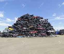 car yard junkyard piled up compressed cars going to be shredded stock photo picture