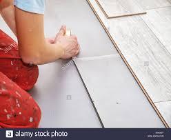 renovating a house handyman laying down laminate flooring boards while renovating a