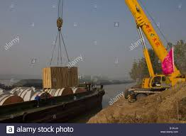 crane lifting large wooden box off a barge at huinanzhuang pumping