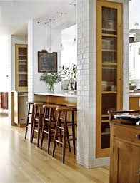 the kitchen island is bookended with brick columns to create more