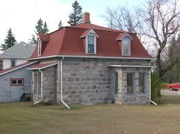 exterior stone exterior siding and mansard roof with dormer