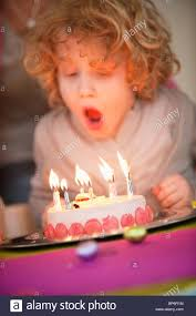 boy blowing out candles on his birthday cake stock photo royalty