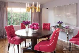 pink tufted dining chairs and lucite and brass chandelier