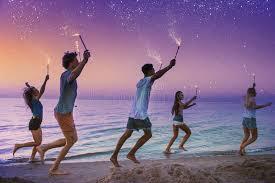 candele scintillanti amici sorridenti felici che corrono alla spiaggia con le candele