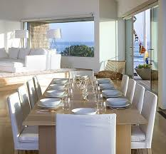 Coastal Dining Room Ideas by Clean White Dining Area With White Upholstered Chairs And
