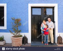 grandparents and grandson 6 8 standing at front door smiling