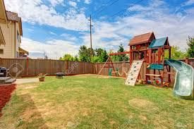 fenced backyard with patio area and playground for kids during
