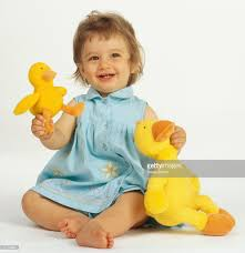 baby in blue dress sitting smiling holding large stuffed duck