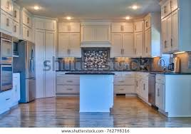 white kitchen cabinets and black stainless steel appliances modern kitchen stainless steel appliances black stock photo