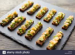 guacamole smoked salmon and rye bread canapes stock photo