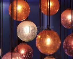 light blue decorative balls orange decorative balls hang against a deep blue background stock