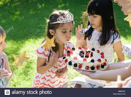 blowing out candles on birthday cake at outdoor birthday