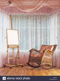 wooden easel and wicker rocking chair composition stock photo