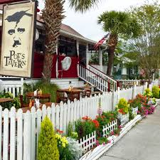 flowers and picket fence in front of cafe and picnic tables at