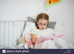 Girls In Bed by Little In Glasses Reading A Book While Lying In Bed Next To