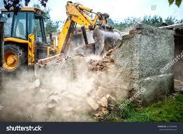 bulldozer demolishing concrete brick walls small stock photo