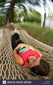 blur motion image of young woman swinging in a hammock and reading
