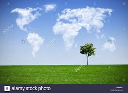 World Cloud Map by Clouds In The Shape Of A World Map Against Blue Sky Stock Photo