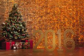 letters u00272016 u0027 and decorated christmas tree on brick wall