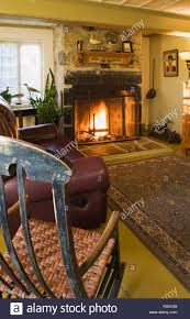 Old Leather Sofa Antique Rocking Chair And Leather Sofa With Lit Fireplace In The