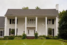 an old white colonial house with columns stock photo picture and
