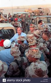 us president george bush leans on the of a humvee as he talks