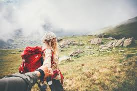 Couple travelers man and woman follow holding hands stock image