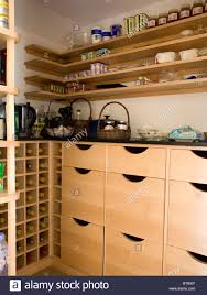 simple wooden shelving above pale wood storage drawers in corner
