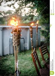 burning tiki torch in the backyard stock photo image 43310341