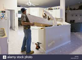 two men lift formica counter top from cabinets in modern kitchen