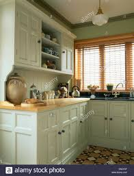 farrow and ball painted kitchen cabinets slatted wooden blind on window in kitchen in traditional pastel