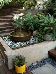 modern backyard ideas with round stone water fountain design and