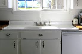 white solid wood kitchen cabinet with white porcelain undermount