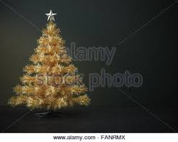 christmas tree decorated with gold and green bell balls in front