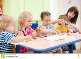 kids learning arts and crafts in kindergarten with teacher stock