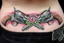 beautiful crossed guns and red rose tattoos on lowerback