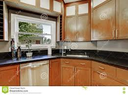 close up of kitchen cabinets black counter top small window