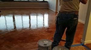 applying second coat of polyurethane on hardwood floors