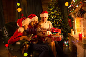 family exchanging gifts in front of fireplace at christmas tree
