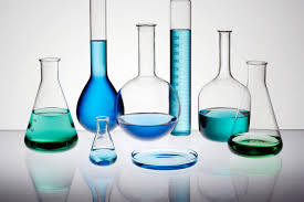 flasks and graduated cylinders filled with a clear blue substance