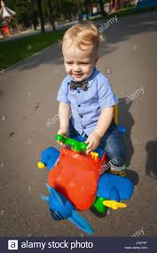 kid play car little blond kid boy driving color toy car and having fun outdoors
