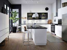 a large modern kitchen with white drawers black smoked glass